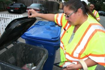 worker looking in garbage bin